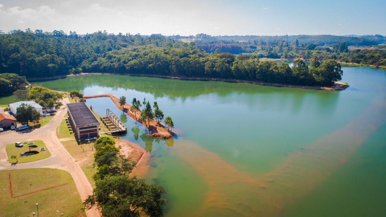 Foto aérea de lago,com árvores e alguns prédios no entorno