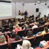 Auditórios com pessoas sentadas e das mulheres em pé, sobre palco, fazendo apresentação