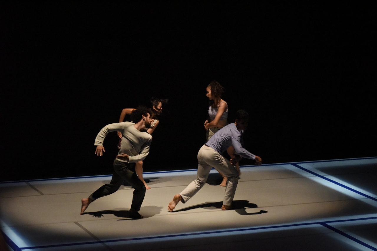 Quatro pessoas dançando sobre tablado,com foco de luz sobre eles e escuro em todo o entorno