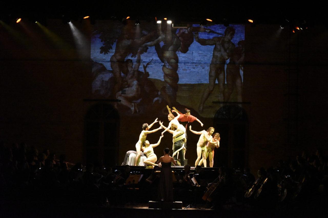 Palco de teatro no escuro, com músicos de orquestra se apresentando, enquanto atores sob feixe de luz reproduzem imagem projetada sobre a parede de fundo