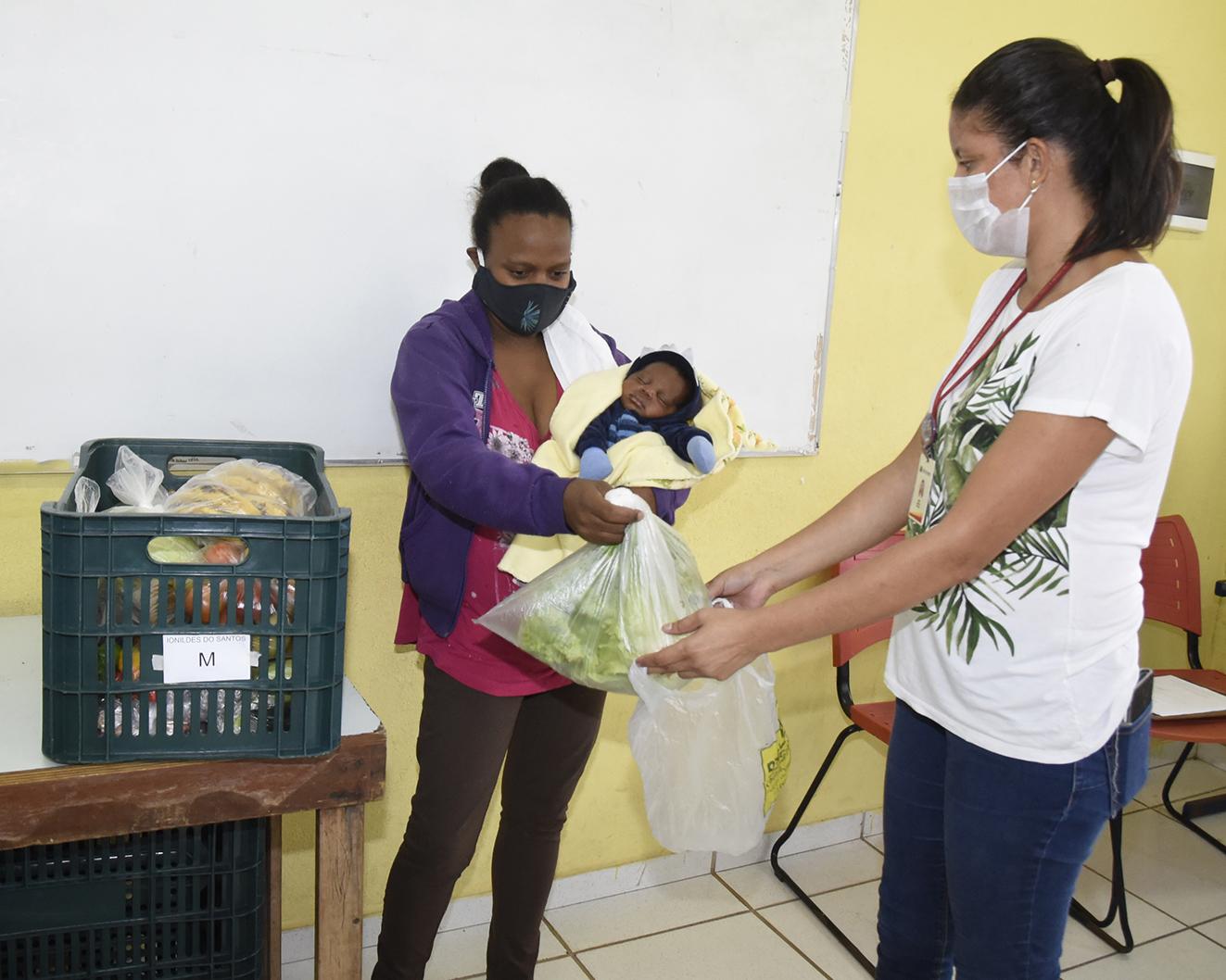 Mulher com criança no colo coloca maço de verdura em sacola que outra mulher segura. Ao lado, sobre uma mesa, há uma caixa de plástico com alimentos ensacados dentro