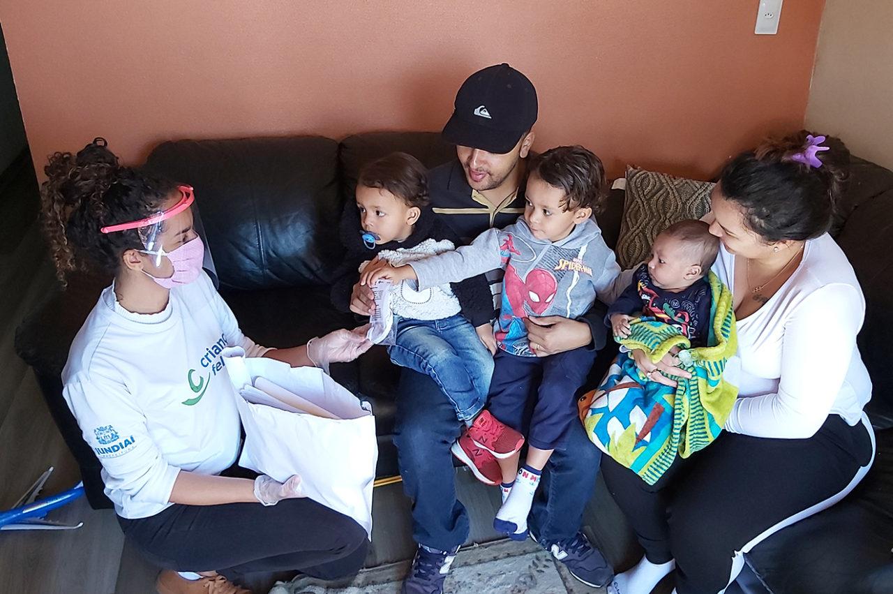 Moça agachada, com máscara e protetor acrílico no rosto, entrega pacotes para casal sentado em sofás, com três meninos de colo