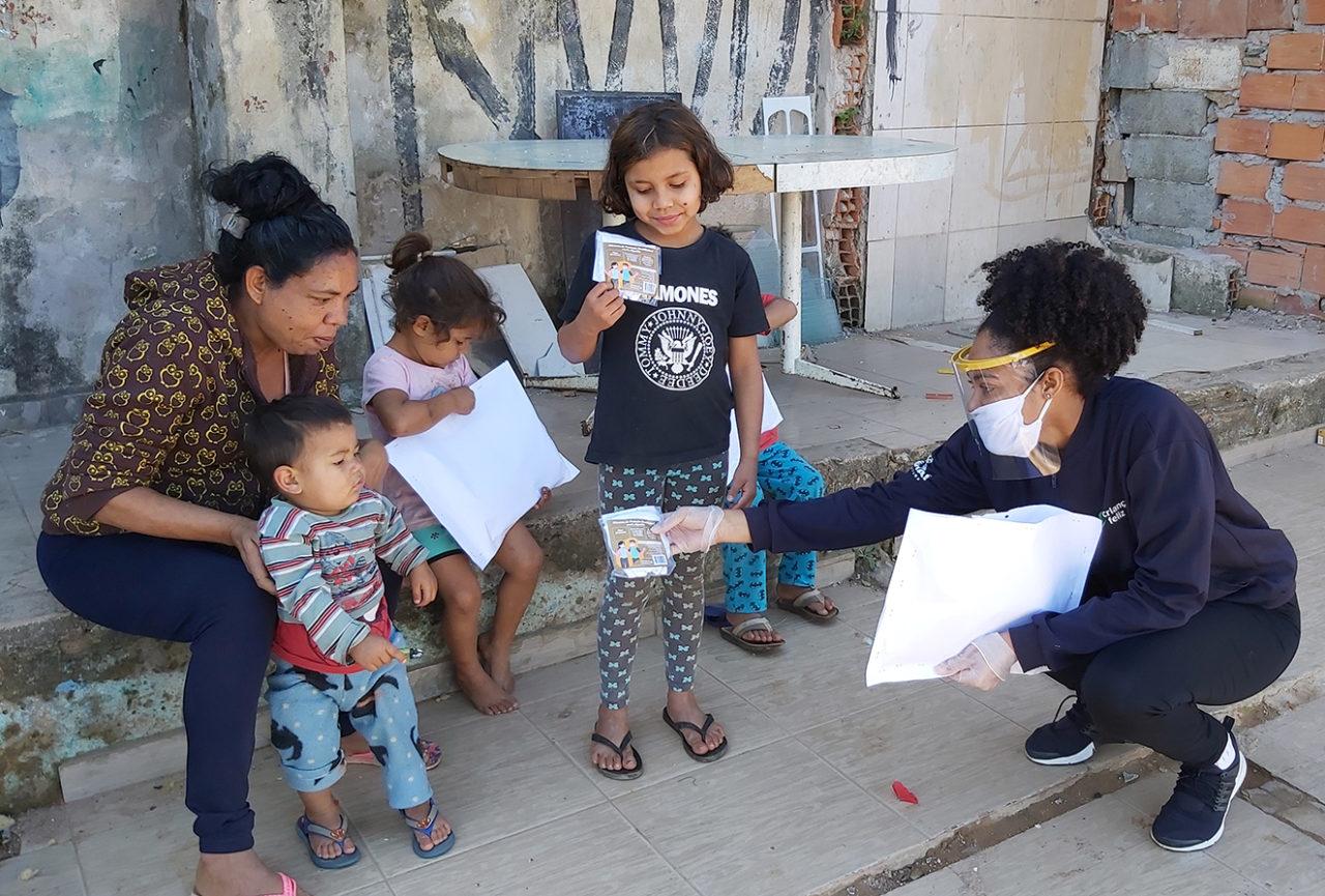 Mulher sentada à beira da calçada, com crianças em torno, com mulher agachada, usando máscara e proteção de acrílico no rosto, entregando pequenos pacotes