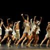 Grupo de bailarinos em performance sobre palco