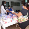 Mulher entrega pequeno para mulher de costas, separadas por uma mesa com pacotes com alimentos
