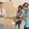 Mulher entrega caixa fechada a casal, com sacola com maçãs em cima
