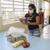 Mulher usando máscara manuseia embalagem de molho de tomate, com sacola de alimento, caixa de ovo e sacola de maçã sobre a mesa