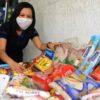 Diretora da escola com máscara, agachada, ao lado dos alimentos arrecadados
