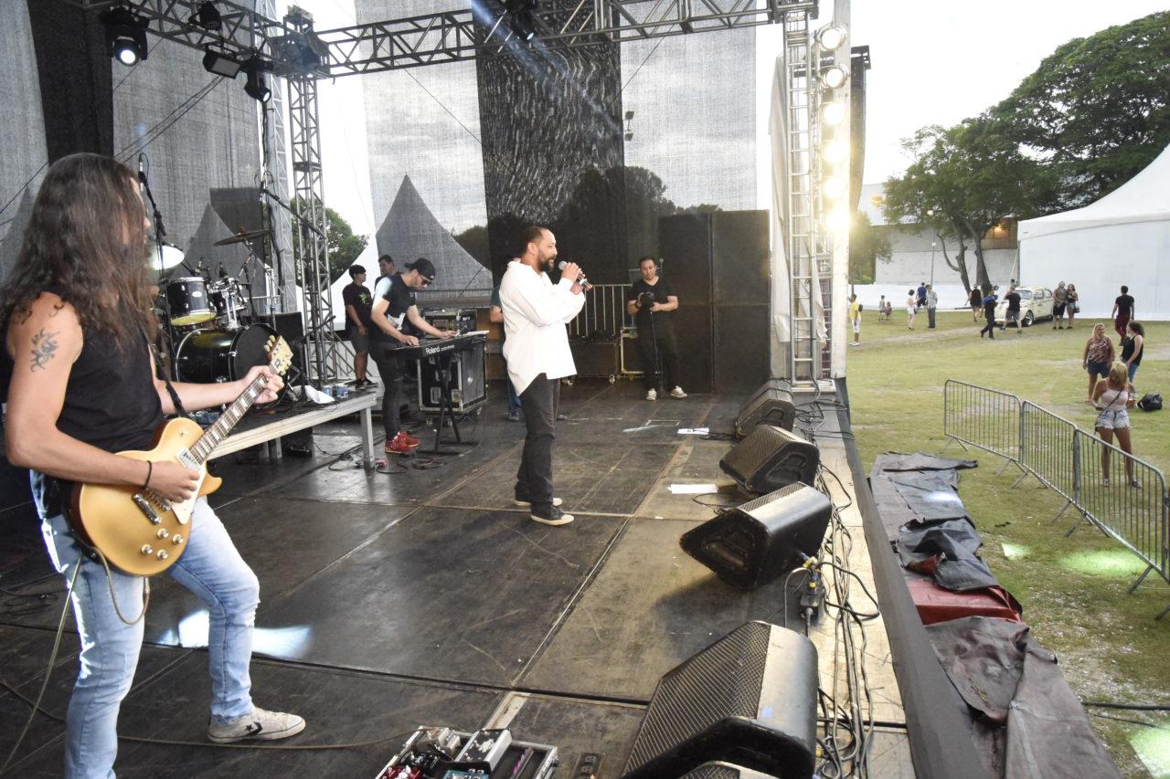 Palco com banda se apresentando, com cantor, guitarrista e outros músicos, com público acompanhando de campo com gramado