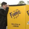 Jovem abre geladeira posicionada em local aberto, com traseira de ônibus ao fundo