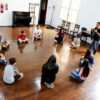 Tablado de madeira, com pessoas em círculo em atividade de aula