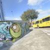 Ônibus passando na rua, com torre e parede grafitada ao lado