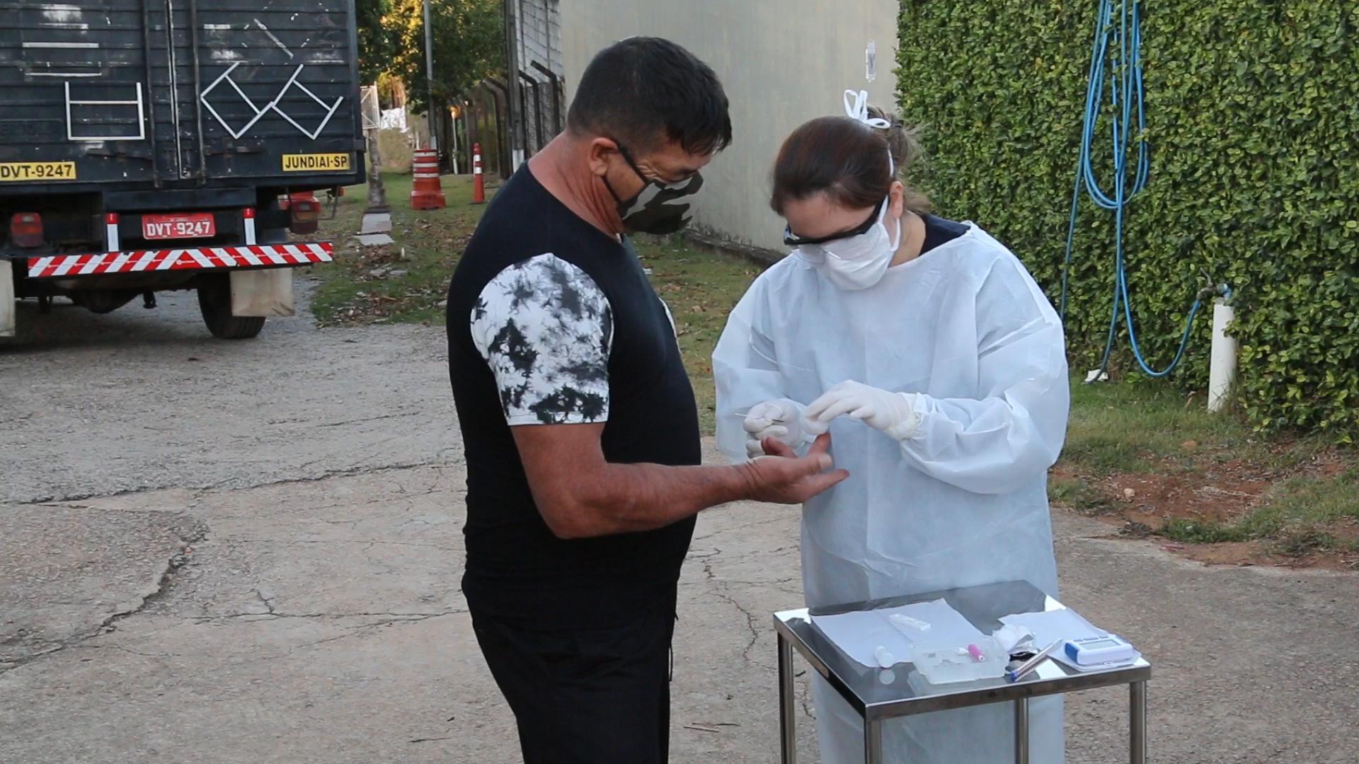 Mulher com roupa de procedimentos médicos faz teste em dedo de homem usando máscara
