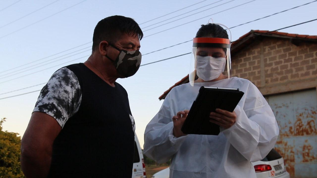 Homem usando máscara sendo entrevistado por mulher com roupas de procedimentos médicos