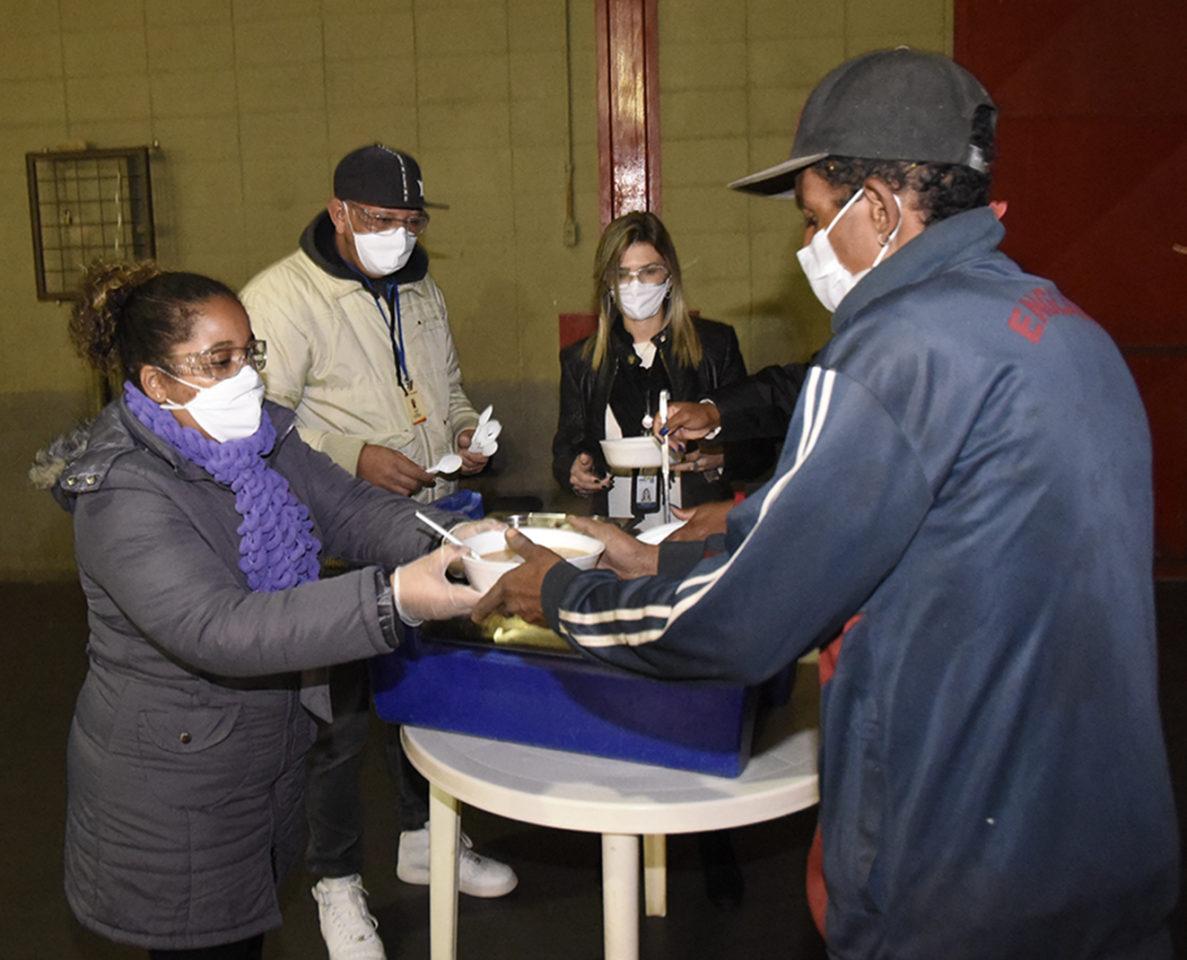 Três pessoas com máscaras e óculos oferecem recipiente com sopa para rapaz de lado com máscara e boné