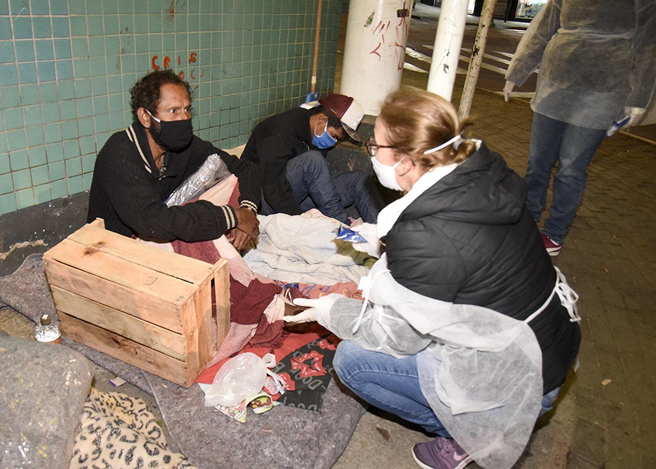 Mulher com avental e máscara abaixada, conversando com dois homens deitados sobre cobertores e caixas sobre uma calçada, apoiados em parede de azulejos