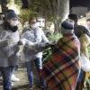 Duas pessoas com aventais e máscaras entregam pacotes a pessoas enroladas em cobertores, em uma praça, à noite