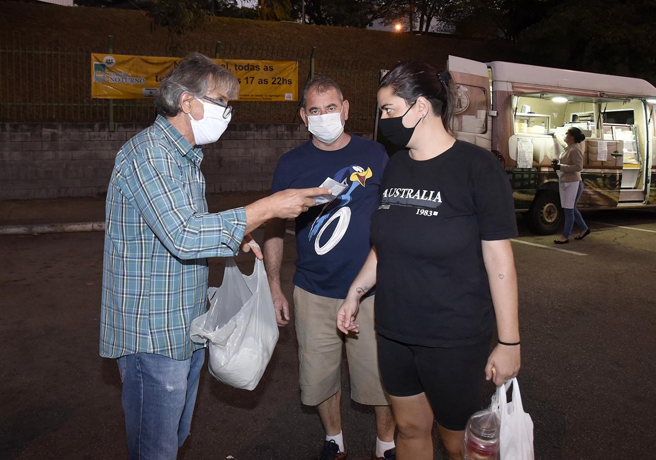 Homem com máscara e roupa xadrez entrega pequeno pacote para homem e mulher, também de máscaras