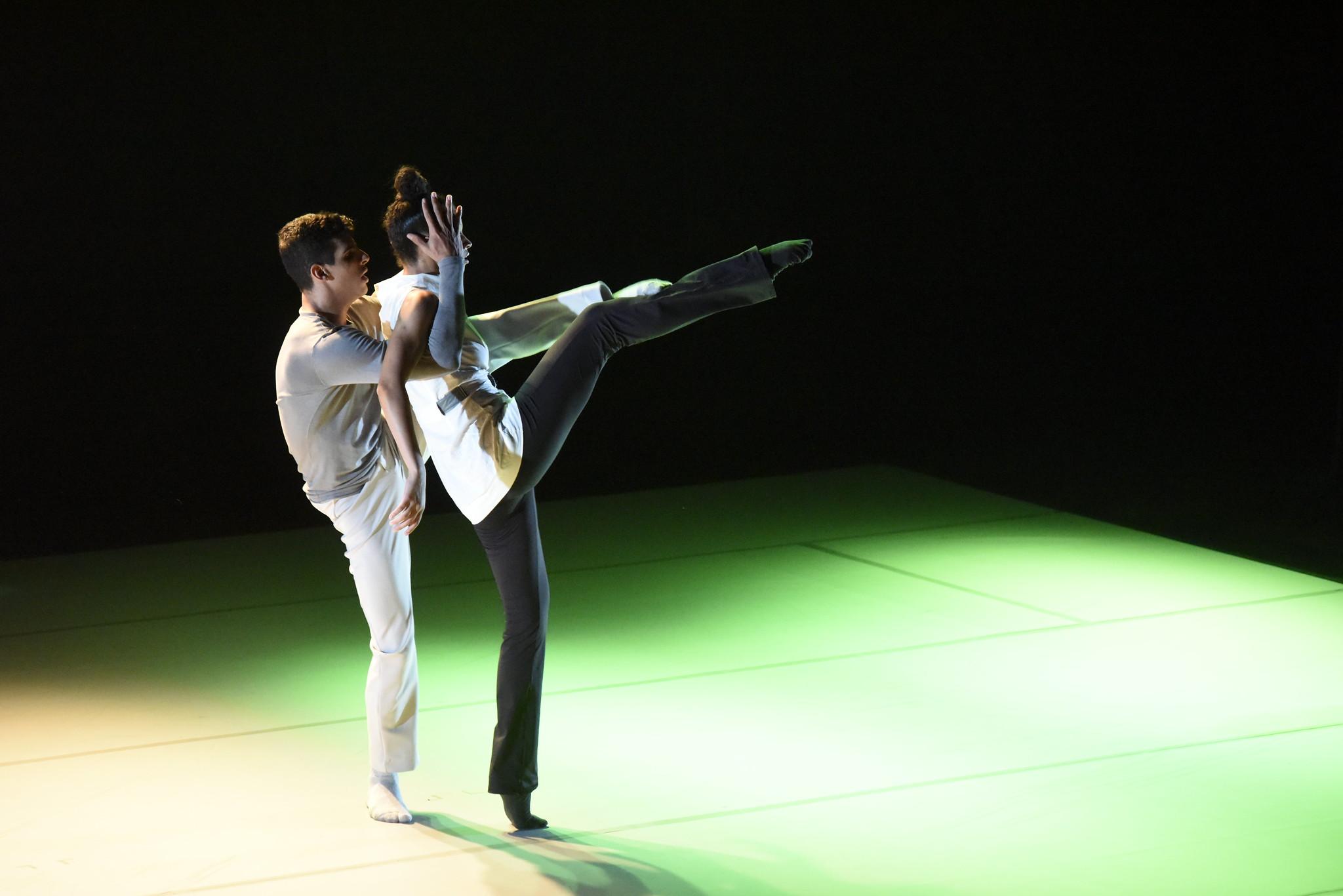 Um casal de bailarinos faz performance sobre palco, um em frente ao outro, ambos com as pernas esquerdas levantadas