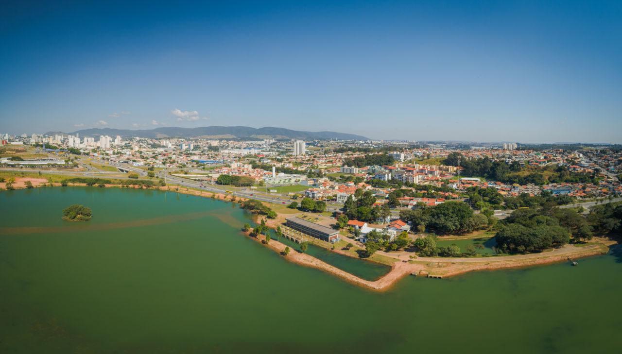 Foto aérea de lagoa, com margem com vias e residências