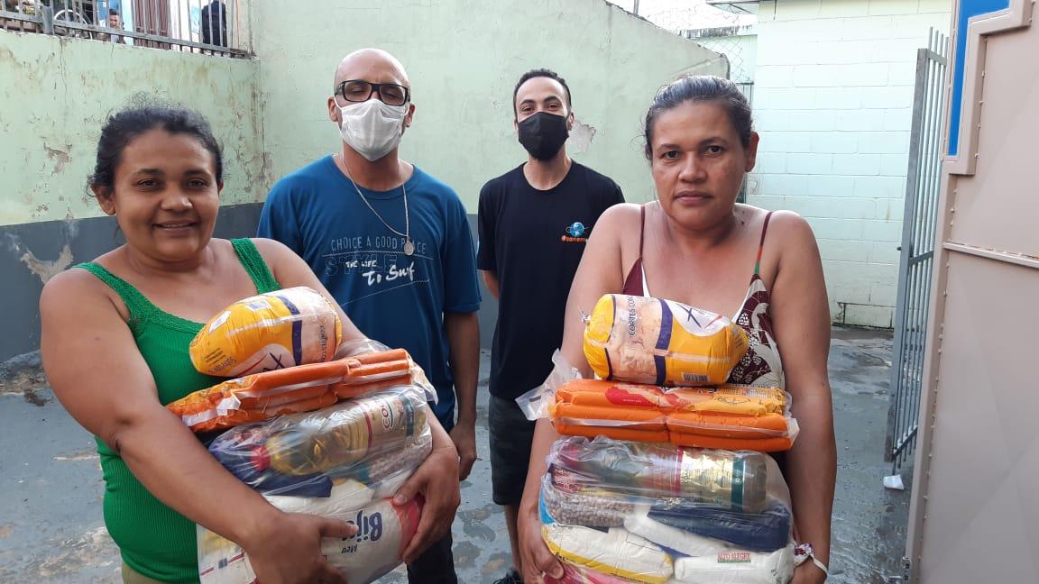 Duas mulheres à frente segurando cestas básicas com alimentos, com dois homens atrás usando máscaras