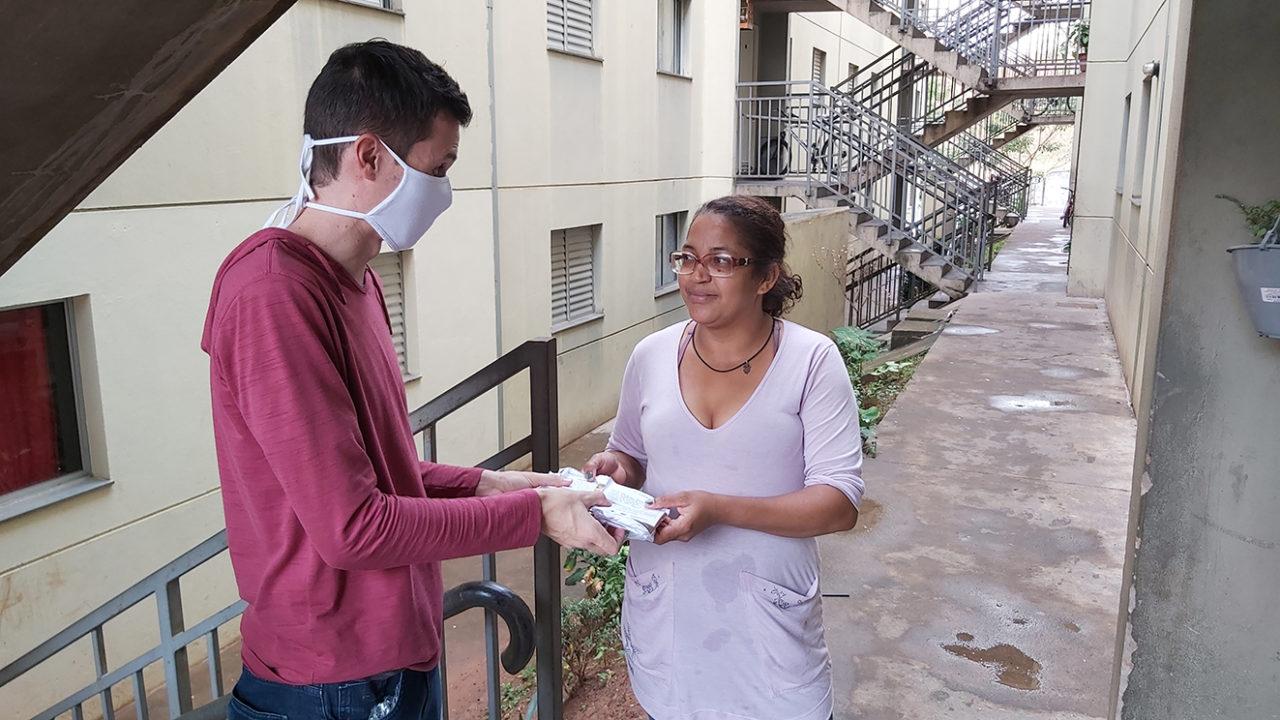 Homem usando máscara entrega pacotes para mulher, com escadaria de prédios ao fundo