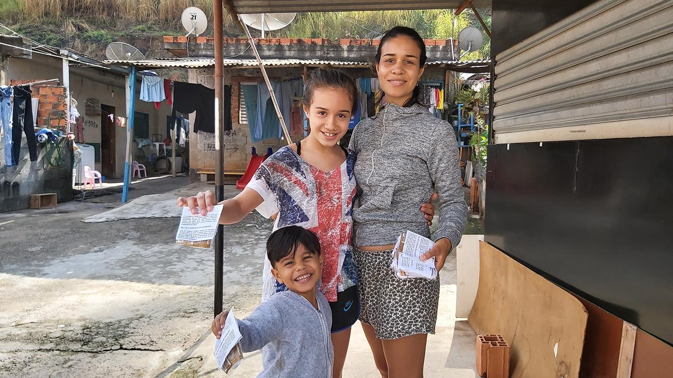 Mulher abraçada com menina e menino pequeno, segurando pequeno pacote, sorrindo, com casa atrás
