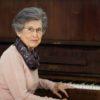 Mulher de cabelo grisalho sentada, apoiando braço esquerdo em teclas de piano