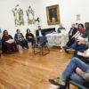 Grupo de pessoas sentadas em semicírculo em sala dentro de prédio antigo, com escultura e espelhos ao fundo
