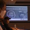 Detalhes de pessoas sentadas, com painel com informações e desenhos ao fundo