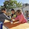 Crianças com agasalhos brincando apoiadas em mesa, em espaço aberto, com céu, árvore e outras crianças ao fundo correndo