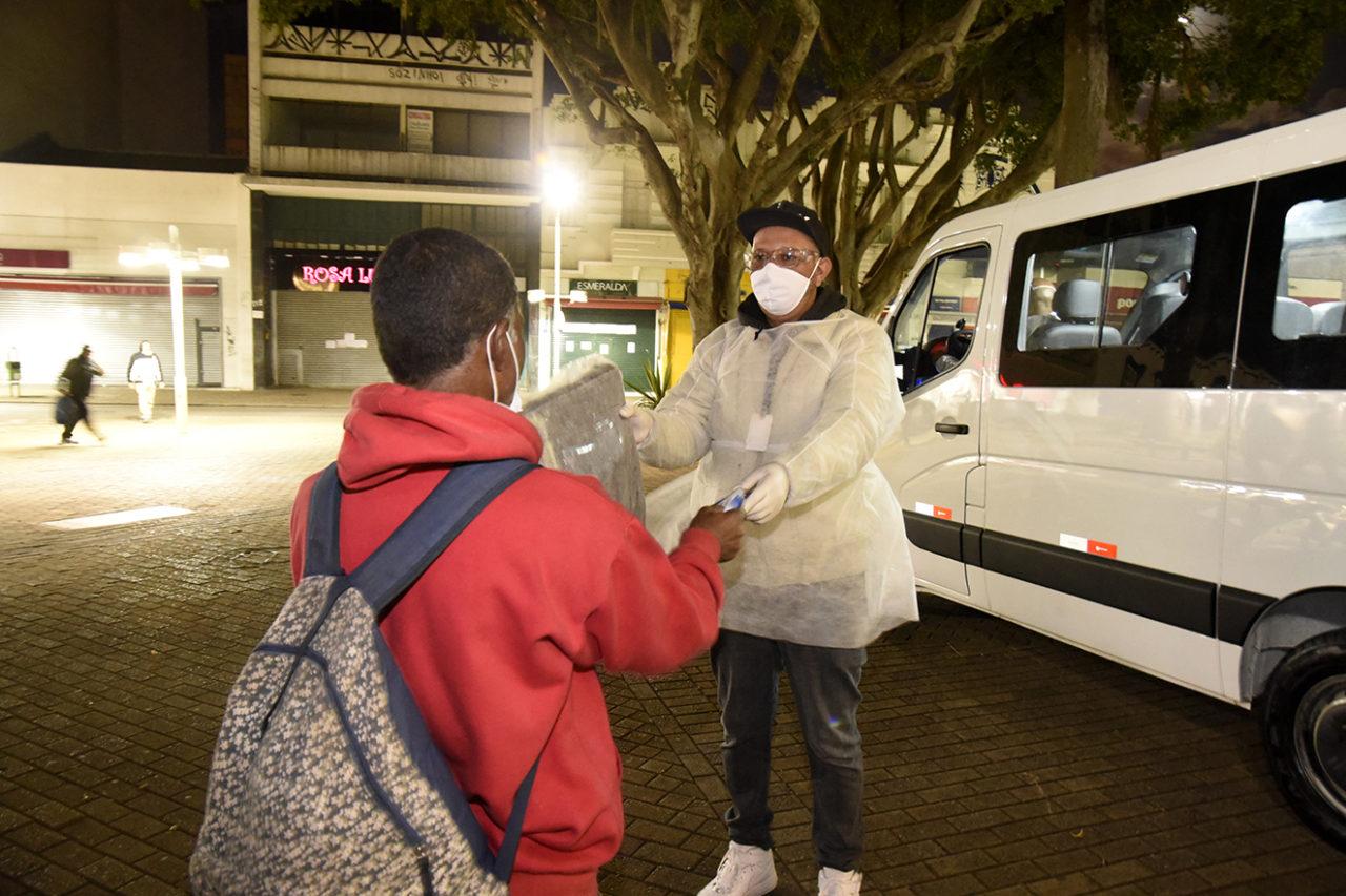 Foto noturna de homem com avental e máscara entrega pacote com cobertor a homem de costas, com van atrás