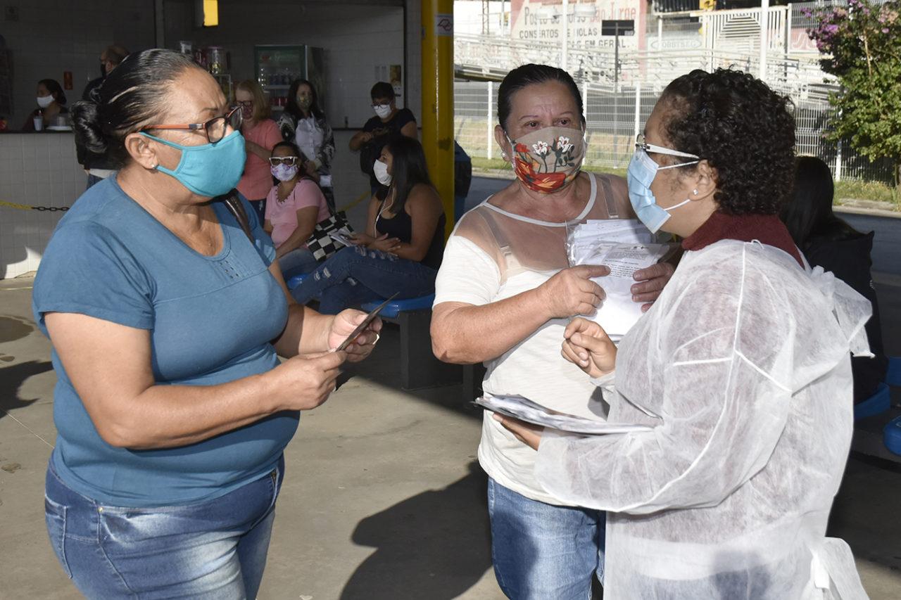 Servidora da Saúde entrega máscara de tecido e folheto explicativo sobre a COVID-19 a passageiras