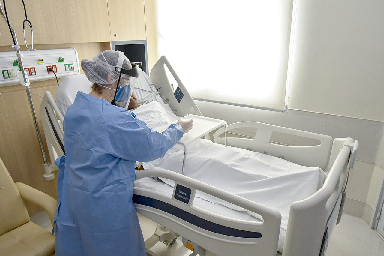 Imagem mostra enfermeira, paramentada com equipamentos de segurança como máscara, face shield, avental, cuidando de paciente deitado em cama hospitarl
