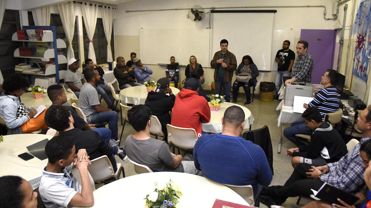 Pessoas sentadas no entorno de mesas, acompanhando uma palestra em uma sala de aula.