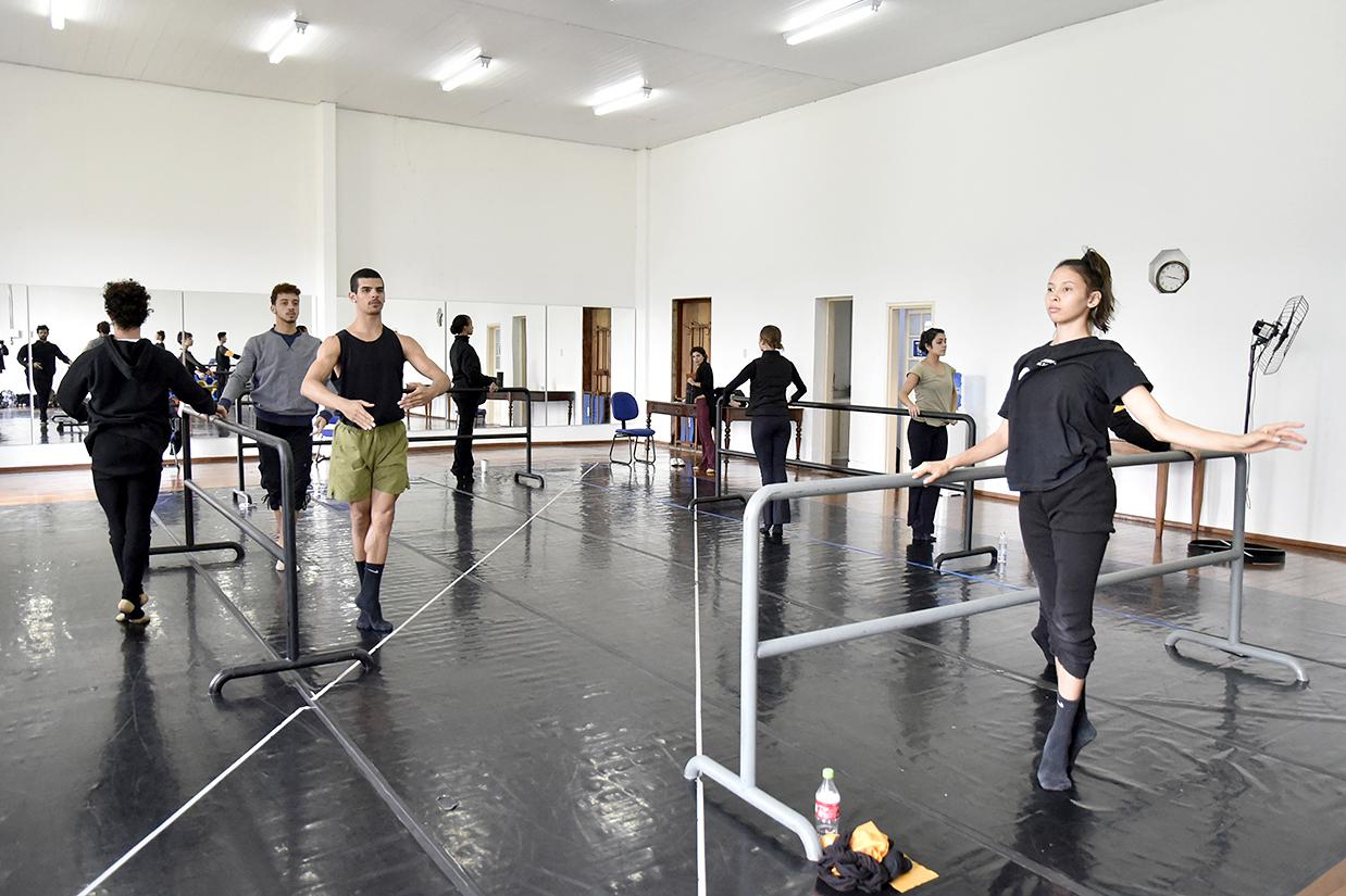 Jovens praticam atividade de dança ao lado de barras em sala ampla, com chão emborrachado e espelhos ao fundo