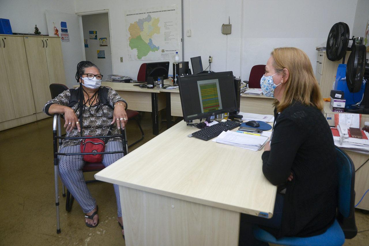 Idosa usando máscara , sentada em cadeira e apoiada em andador é atendida por outra mulher usando máscara, sentada defronte a um computador com planilha na tela
