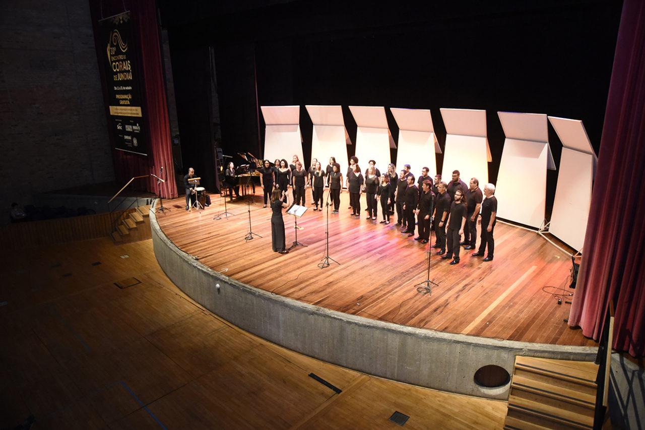 Palco de teatro, com cantores com roupas pretas perfilados, com regente de costas e pessoa ao piano ao fundo