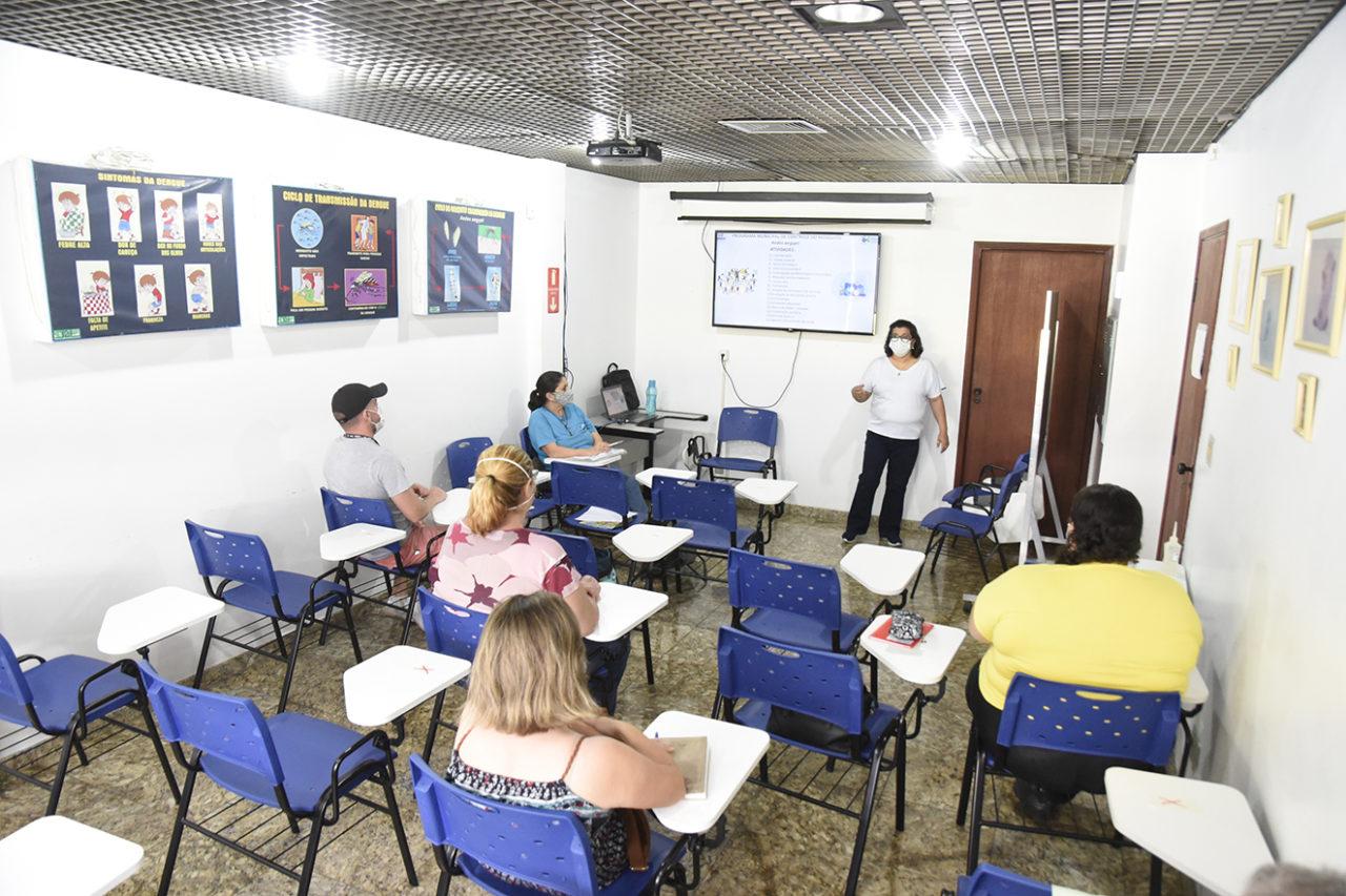 Sala de aula, com pessoas sentadas em cadeiras e mulher em pé, à frente de lousa