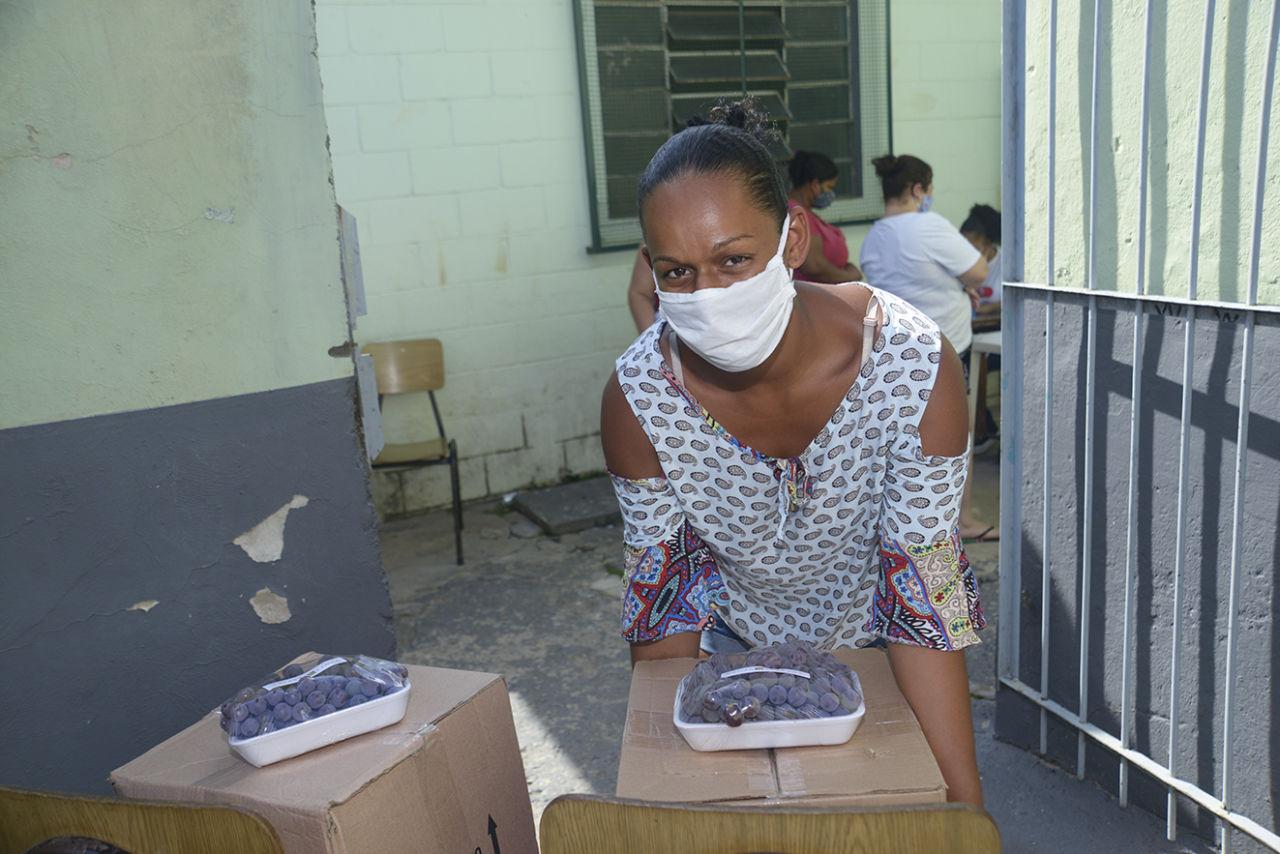 Mulher com máscara olha para câmera enquanto começa a carregar caixa de papelão com bandeja de uvas embalada