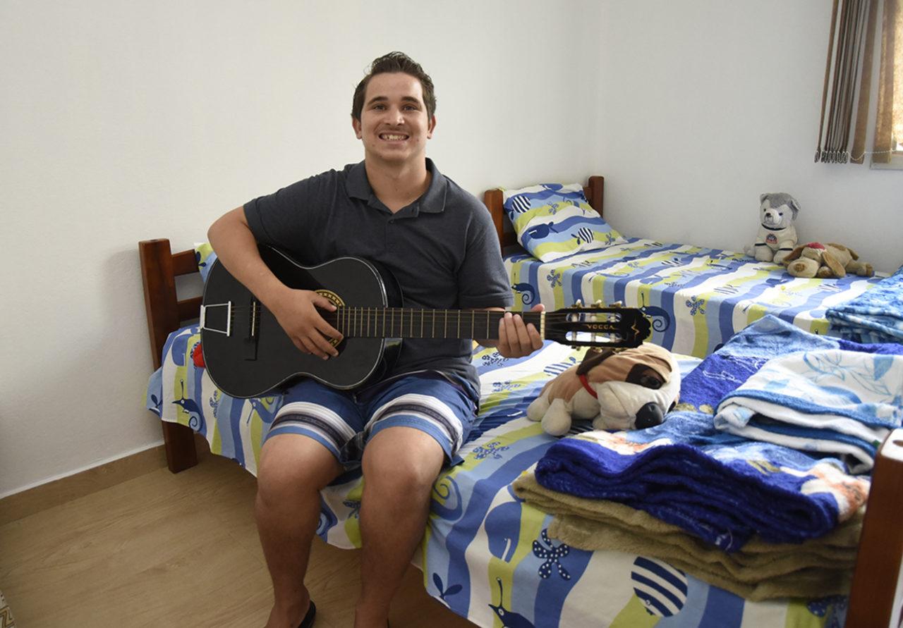 Rapaz sorridente, sentado em cama arrumada, segurando violão.