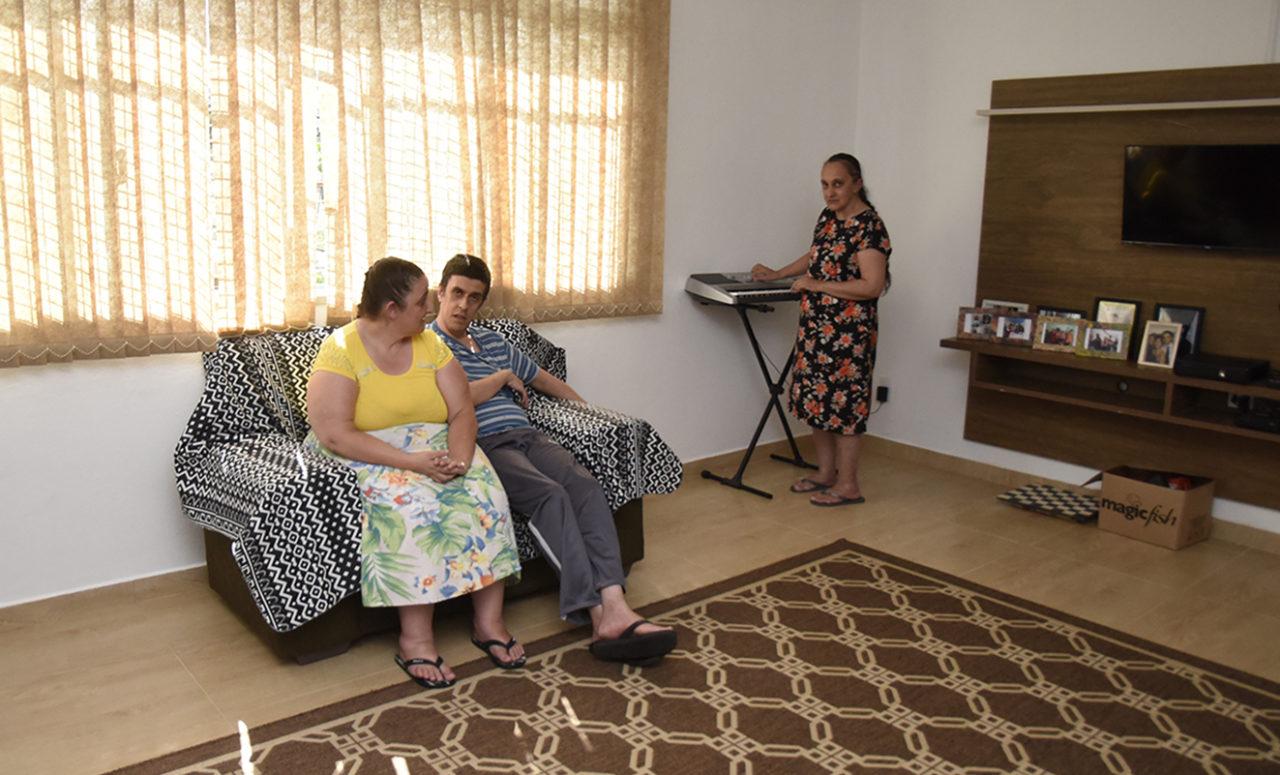 Mulher e homem sentado sobre sofá, com outra mulher em pé interagindo com teclado
