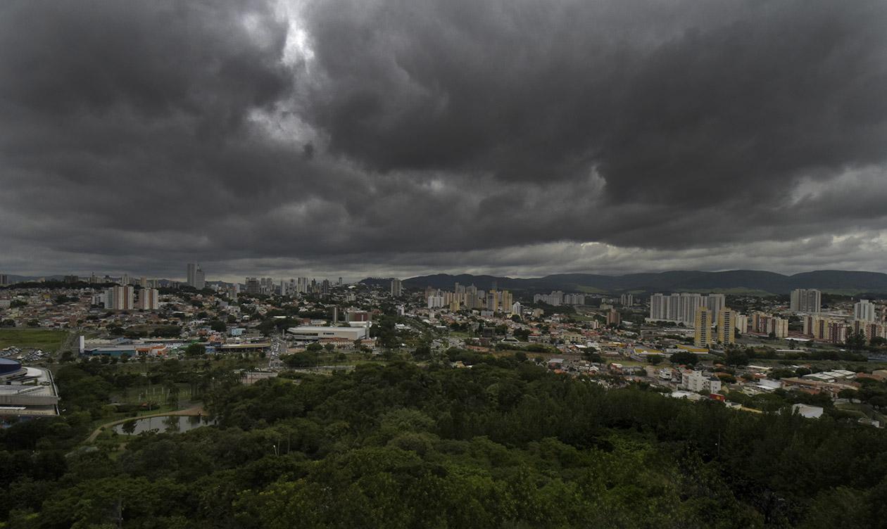Foto panorâmica de cidade com vegetação e edifícios, com nuvens escuras no céu, ameaçando começar a chover.