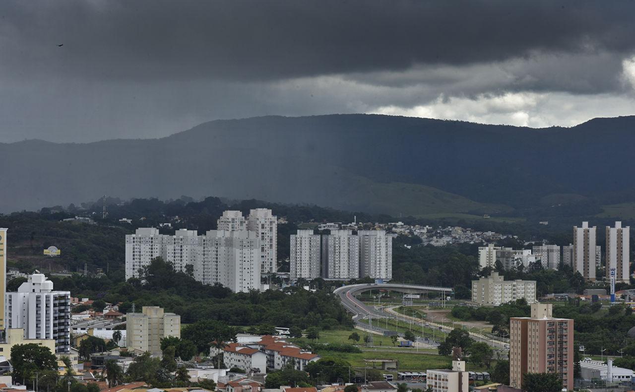 Panorama de cidade com prédios e vias, e com serra ao fundo, e nuvens escuras no céu.