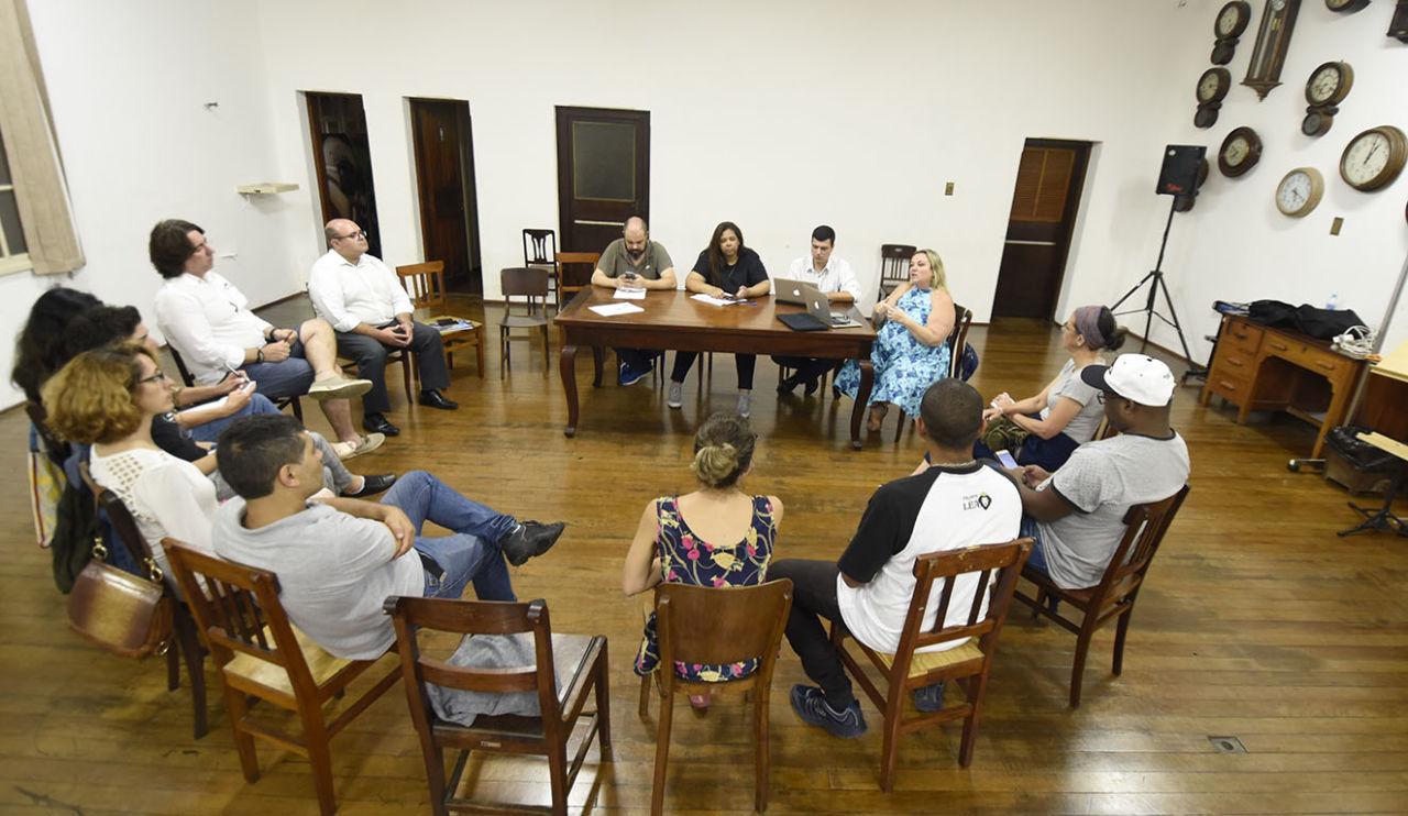 Diversas pessoas sentadas em cadeiras em formato de círculo, sobre chão de madeira
