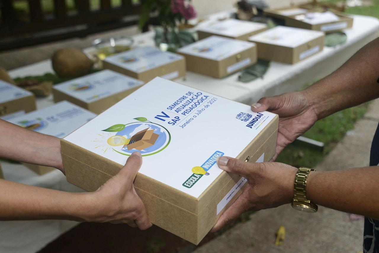 Na foto há uma mão entregando uma caixa-convite do evento para outra mão