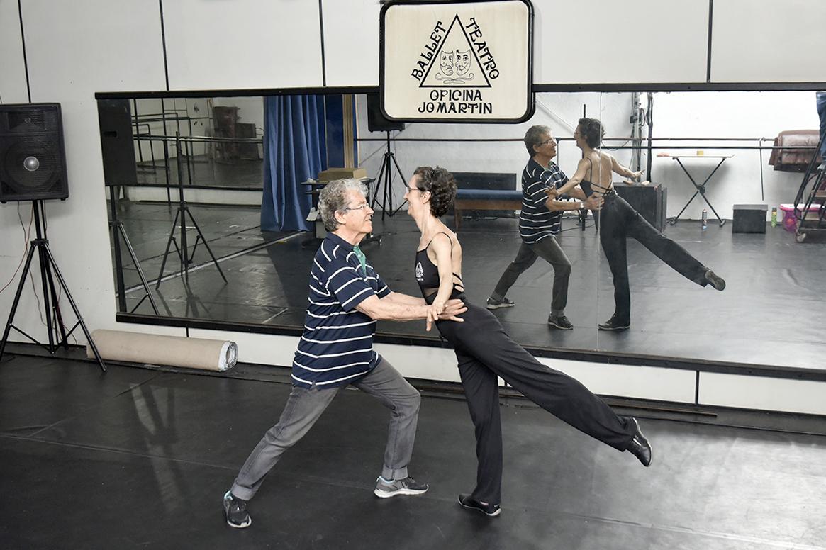 Homem e mulher fazem passo de dança em salão de academia, com imagem refletida em espelho na parede, com caixa de som ao fundo.