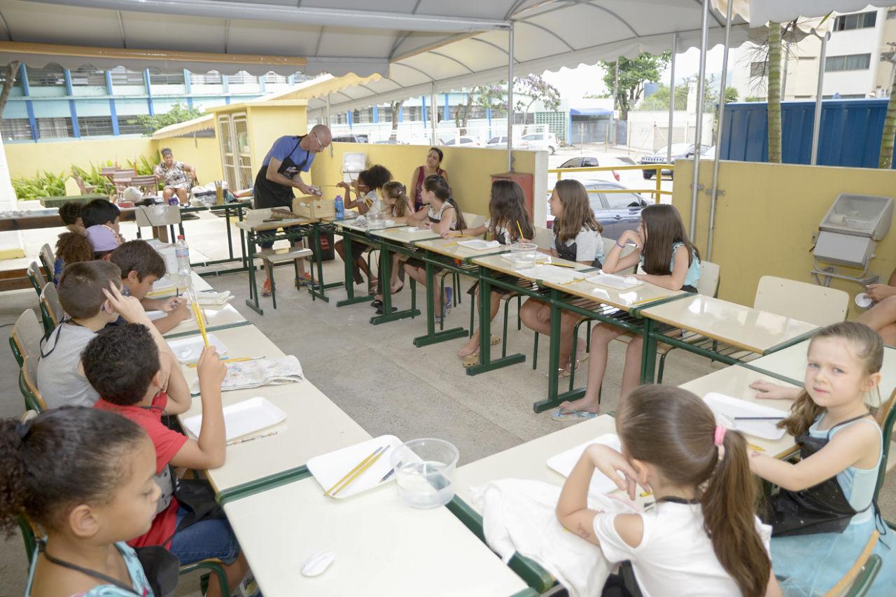 Área externa coberta com crianças sentadas no entorno de mesas com materiais de artesanato, como potes, pincéis e bandejas.