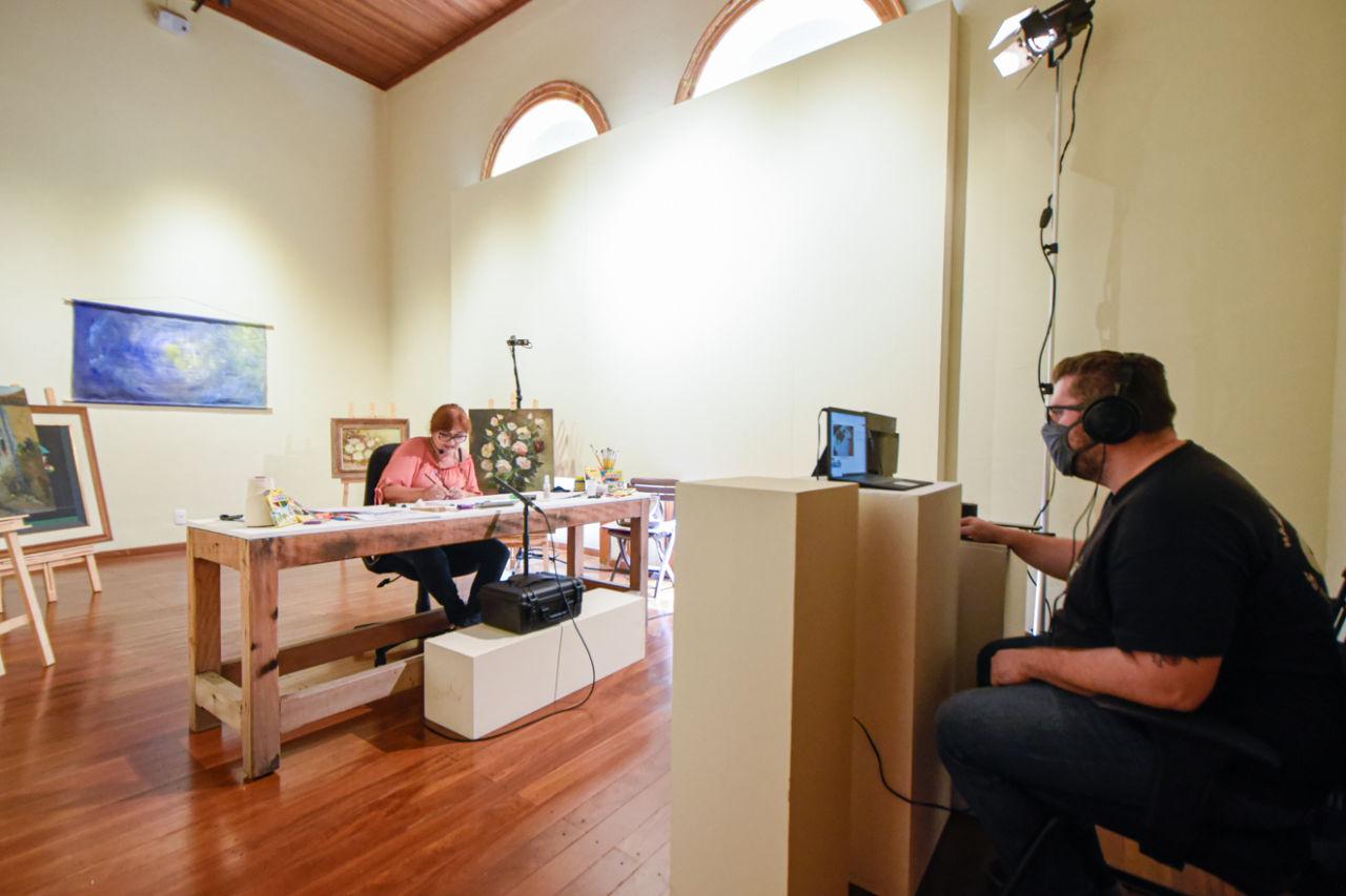 Sala de exposições, com homem controlando operações de vídeo e iluminação, e mulher em frente, atrás de uma mesa e cercada por quadros, faz atividades manuais