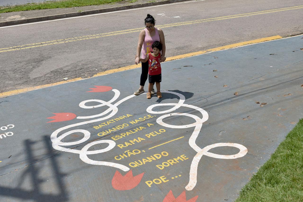 Foto do alto de calçada com poema pintado, com mulher em pé apontando e menino apoiado olhando para o que está escrito